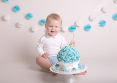 smiling baby boy with a cake