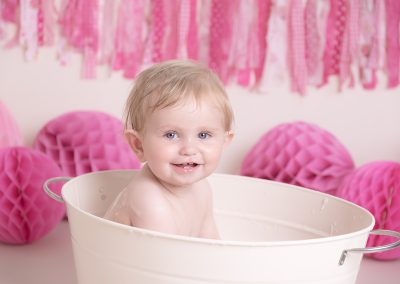baby girl having a bath during her cake smash session