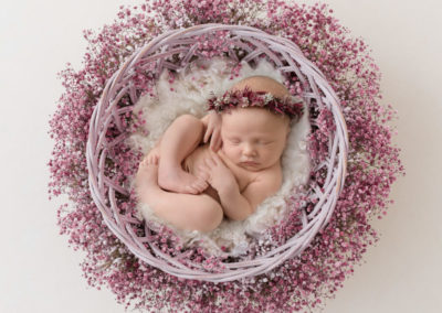 newborn girl laying in a fur nest with flowers