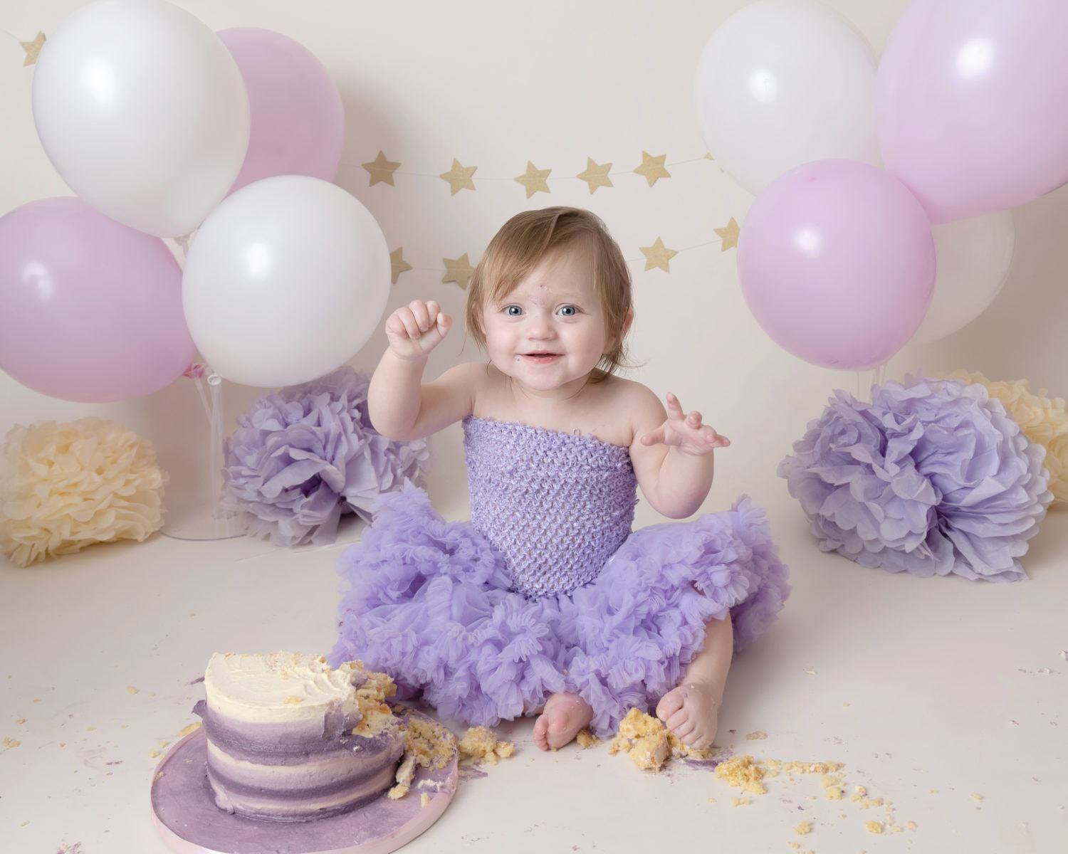 baby girl having fun eating cake