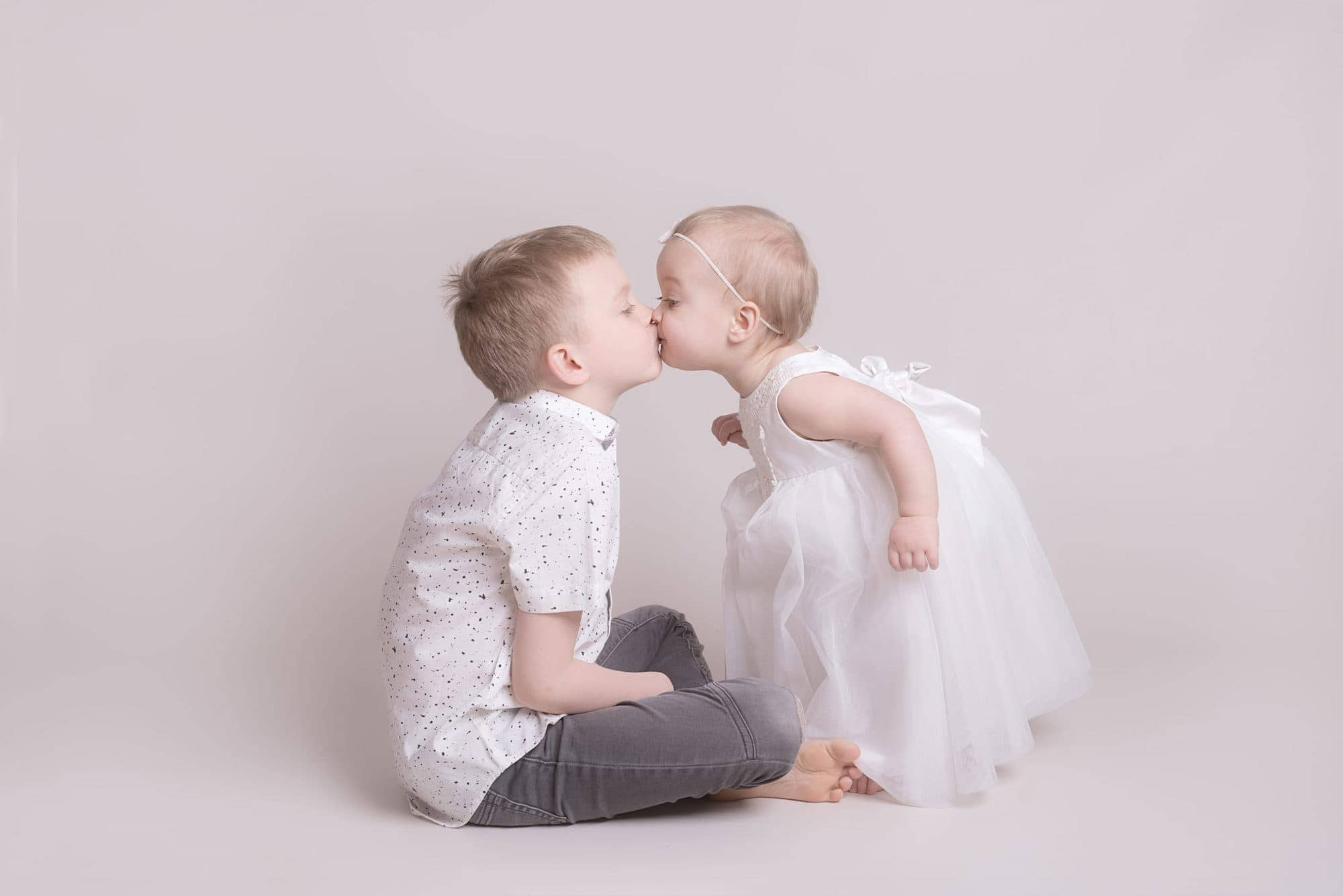 baby girl bending down to give big brother a big kiss
